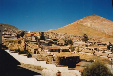 La ville de Potosi, le canal de la Ribera et le Cerro Rico, la montagne d'argent. Vue du centre vers les quartiers hauts traditionnellement de paroisses d'Indiens et donc plus pauvres. L'église de la paroisse San Benito est à gauche tandis que le canal de La Ribera dont l'eau fait tourner toutes les usines de Potosi se devine au premier plan derrière le grand mur blanc. A droite, le grand cône du Cerro Rico (4800 m), qui fut le plus grand gisement d'argent du monde et qui est toujours exploité intensivement par des mines de coopératives ouvrières. ©A. Gioda, IRD, vers 1998.