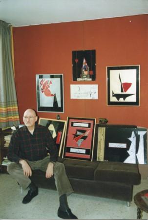 Tristan chez lui, devant quelques-unes de ses réalisations graphiques.